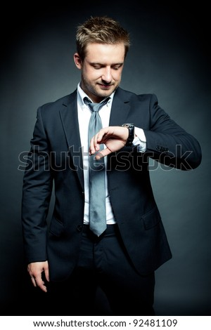 Businessman looking on his watch over dark black background - stock photo