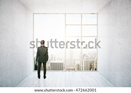 Businessman looking out of big window in interior with concrete walls, white wooden floor and city view. Research concept. 3D Rendering