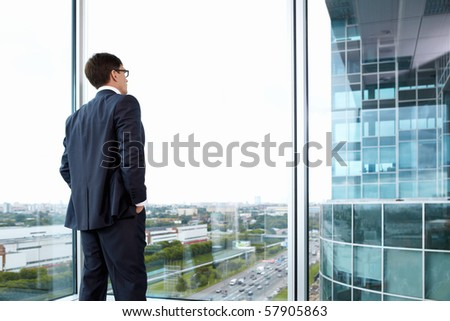 Businessman looking out of his office on the opposite building - stock photo