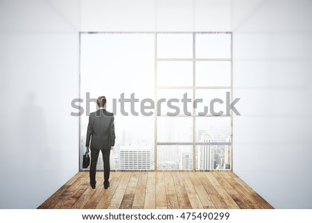 Businessman looking out of large window in interior with concrete walls, wooden floor and city view. Research concept. 3D Rendering