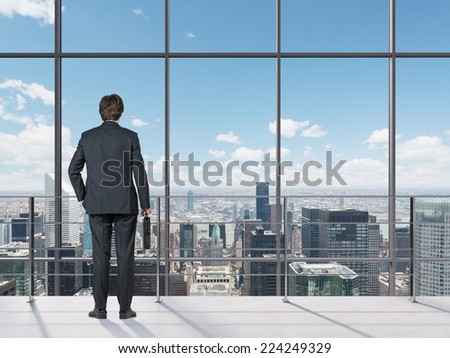 Businessman looking out of office window.