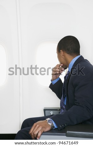 Businessman looking out plane window - stock photo