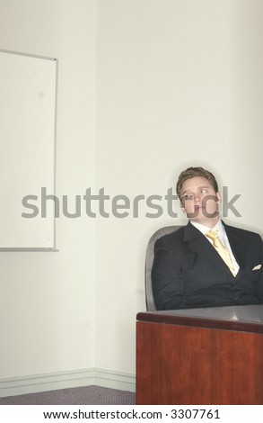 Businessman looking over while sitting in his chair at his desk in the office - stock photo
