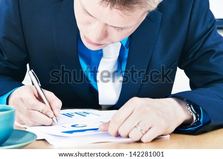 Businessman looking sales report and making notes