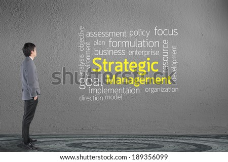 Businessman looking Strategic management text wording in cloud concept