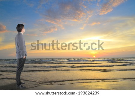 Businessman looking sunset with sea  in vision concept