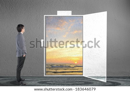 Businessman looking sunset with sea on door opening in vision concept