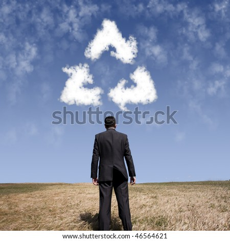 businessman looking the recycle shape clouds at the field - stock photo