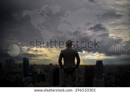 Businessman looking the World map on sky - stock photo
