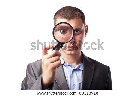 Businessman looking through a magnifying glass isolated on white background