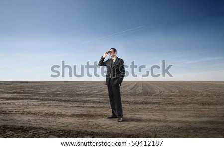 Businessman looking through a pair of binoculars on a field