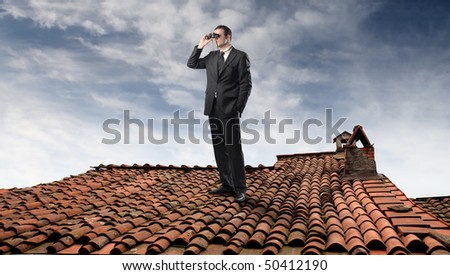Businessman looking through a pair of binoculars on a rooftop - stock photo