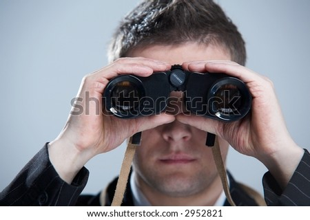 Businessman looking through binoculars - stock photo