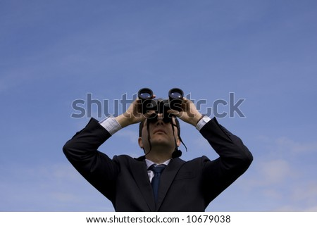 Businessman looking through binoculars with a blue sky as background - stock photo