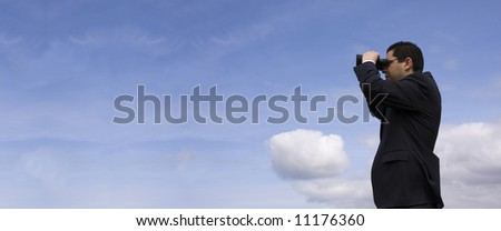 Businessman looking through binoculars with a blue sky as background (panoramic photo) - stock photo