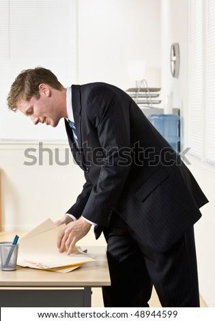 Businessman looking through file folders - stock photo