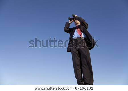 Businessman looking through his binoculars in outdoor - stock photo