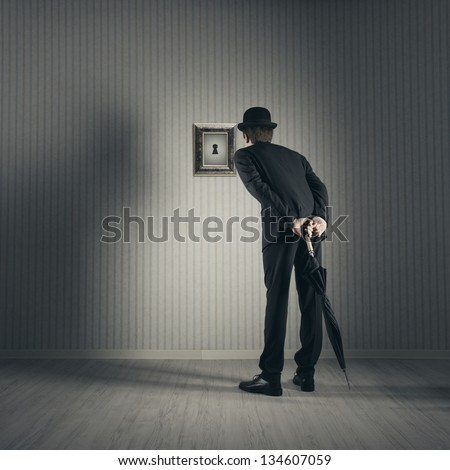 Businessman looking through keyhole - stock photo