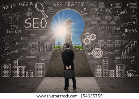 Businessman looking through keyhole with success road with SEO business doodle on blackboard - stock photo
