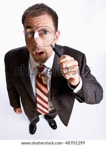 Businessman looking through magnifying glass - stock photo