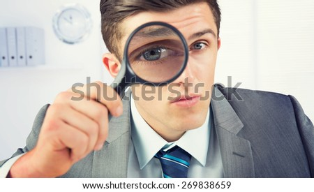 Businessman looking through magnifying glass against a empty office with a laptop