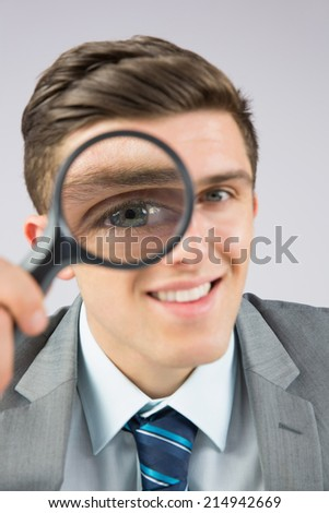 Businessman looking through magnifying glass on grey background - stock photo