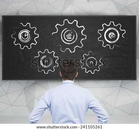 businessman looking to drawing cogs and gears on desk - stock photo