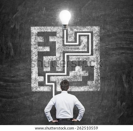 businessman looking to drawing maze on blackboard - stock photo