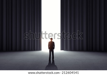 businessman looking to open curtains in room - stock photo