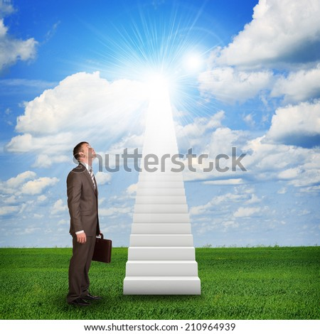 Businessman looking to stairs in sky - stock photo