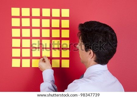 Businessman looking to yellow papers stick at a red wall - stock photo