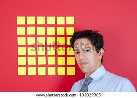 Businessman looking to yellow papers stickied at a red wall - stock photo