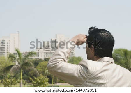 Businessman looking towards a city with shielding eyes - stock photo