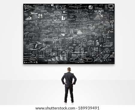 businessman looking up at blackboard with business plan - stock photo