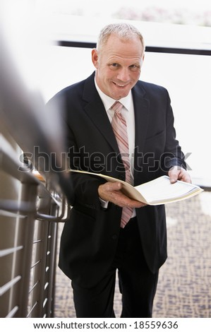 Businessman looking up from paperwork near office stairs - stock photo