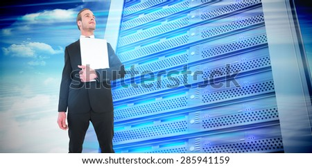 Businessman looking up holding laptop against composite image of server tower - stock photo