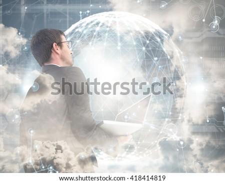 Businessman looking up holding laptop against hologram background - stock photo