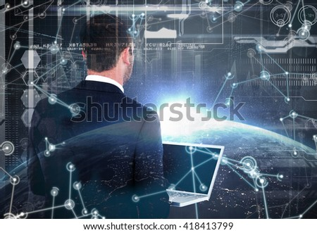Businessman looking up holding laptop against image of a earth - stock photo