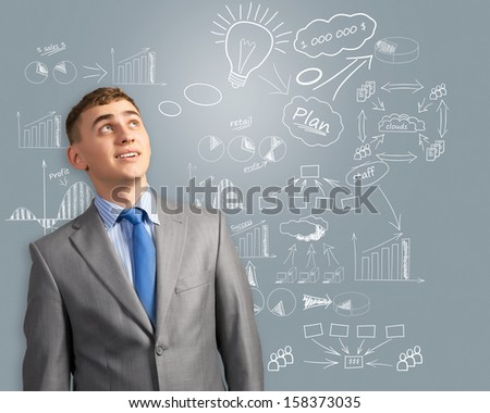 businessman looking up, thinking about innovation in business, an outline on the wall of charts and diagrams
