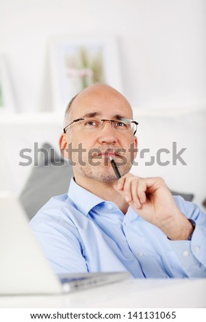 Businessman looking up with pen on his chin at home - stock photo