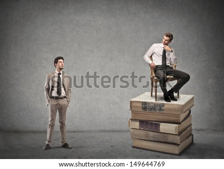 businessman looks another businessman sitting high on a stack of books - stock photo