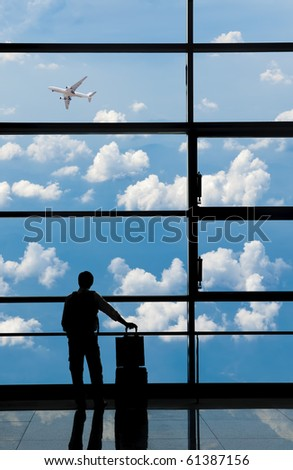 Businessman looks at airplane at airport's departure area. - stock photo