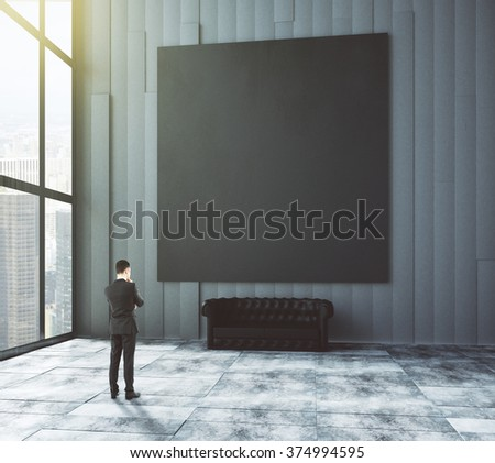 Businessman looks at big blank picture above leather sofa in empty loft room with big windows and concrete floor 3D Render - stock photo