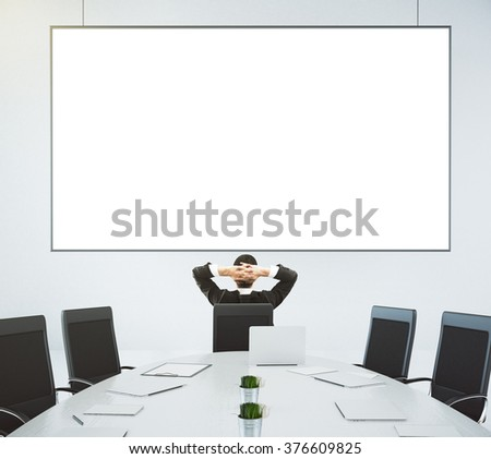 Businessman looks at blank poster on the wall in modern conference room, mock up - stock photo