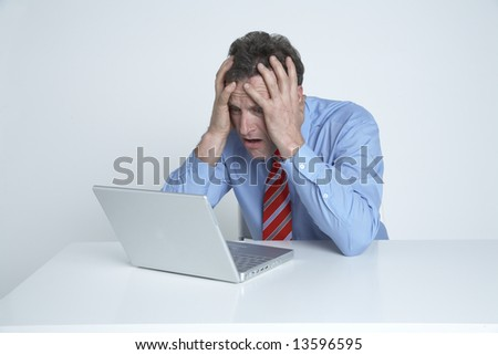 Businessman looks at his computer in disbelief - stock photo