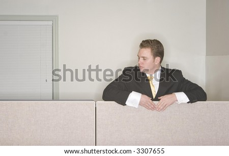 Businessman looks down from  his cubicle in his office while wearing a black suit and gold tie