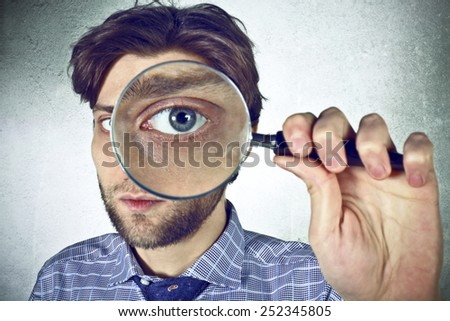 Businessman looks through a magnifying lens