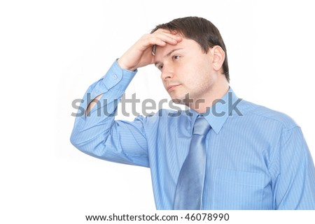 Businessman looks up in despair, scratching his head - stock photo