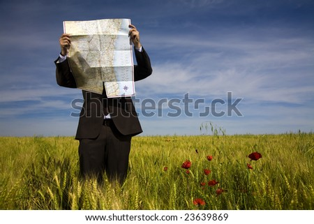 businessman lost in field using a map - stock photo