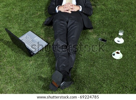 businessman lying in a park with his laptop - stock photo